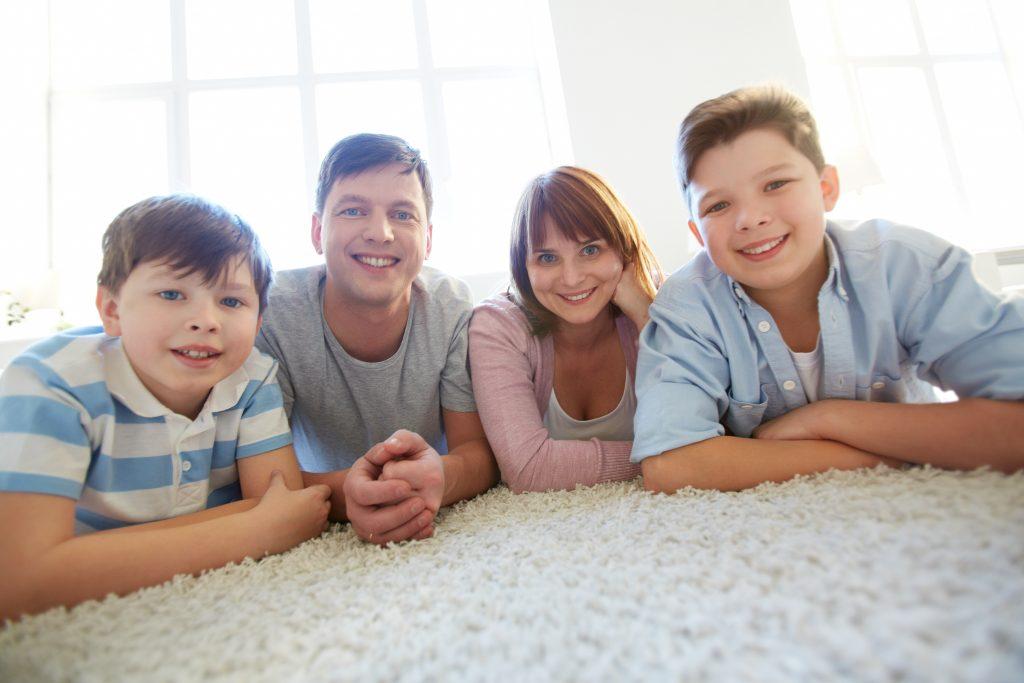 משפחה שמחה על שטיח נקי